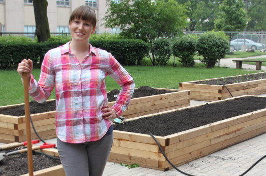 Garden director Renea Solis standing beside a raise garden bed containing growing herbs