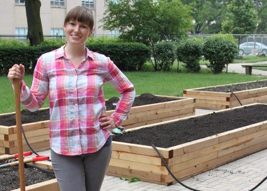 Garden director Renea Solis standing beside a raise garden bed containing growing herbs