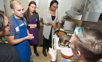Students in aprons standing around stove while food cooks in pans