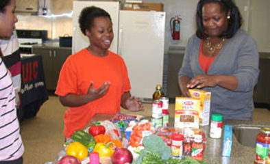 Three women stand around a kitchen counter filled with a variety of food