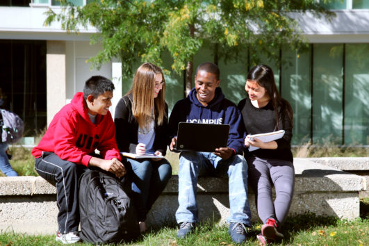 A group of UIC students gather around a laptop screen while sitting outside