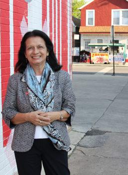 Yolanda Suarez-Balcazar leans against a building wall. The background shows a city crosswalk