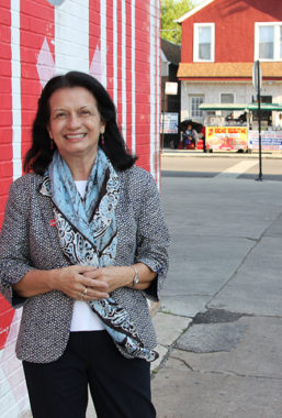 Yolanda Suarez-Balcazar leans against a building wall. The background shows a city crosswalk