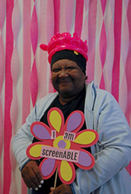 """ScreenABLE attendee standing up holding a sign that reads """"I am screeable"""""""