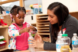 Woman helping young girl working with water bottle