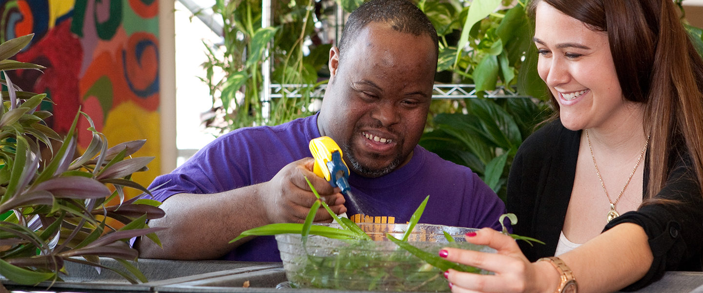 Woman working with plants with African-American man with disabilities