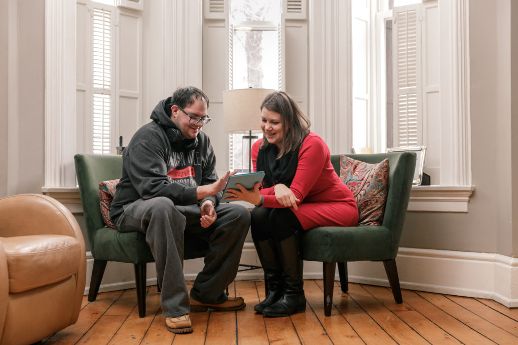 Women reading with man with disabilities