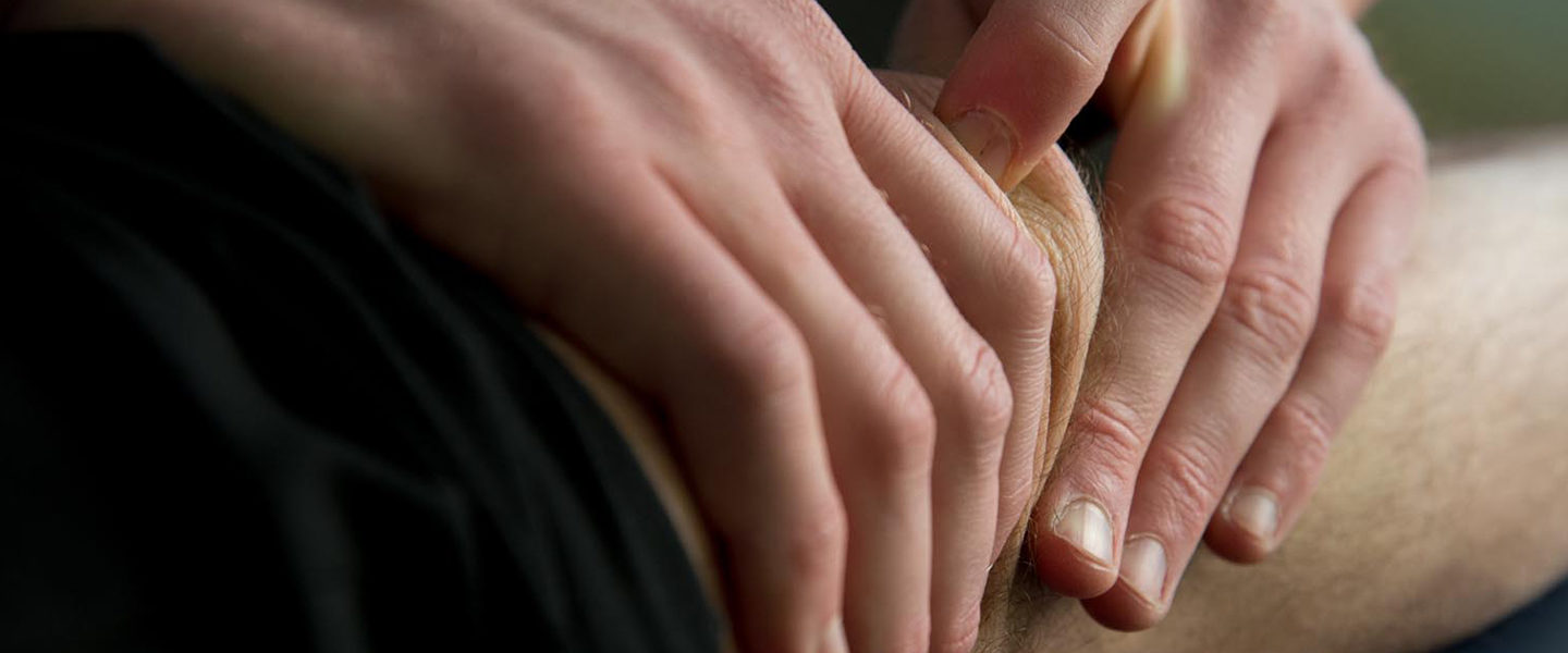 Hands of a physical therapist manipulating a patient's knee