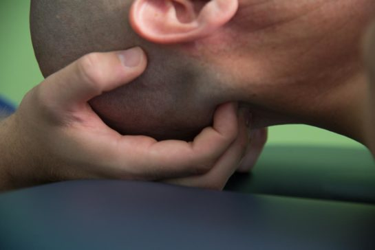 Hands of a physical therapist manipulating a patient's neck