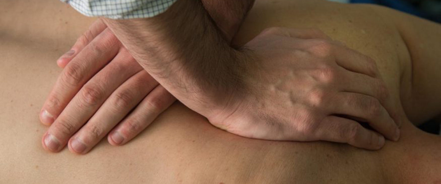 Hands of a physical therapist manipulating a patient's back