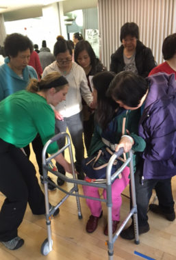 A student trains a group of home healthcare nurses with using an assisted walking device