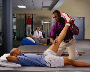 A physical therapist manipulates a client's knee