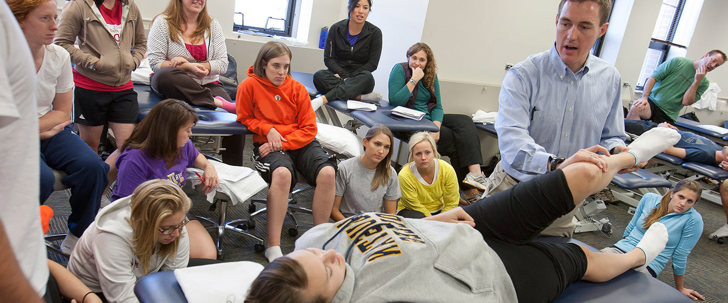 Physical therapy professor and students in a hands-on classroom