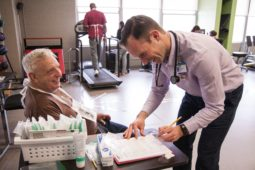 Cemal Ozemek (right) checks the vitals of a cardiac rehabilitation patient (left) while discussing an exercise plan.