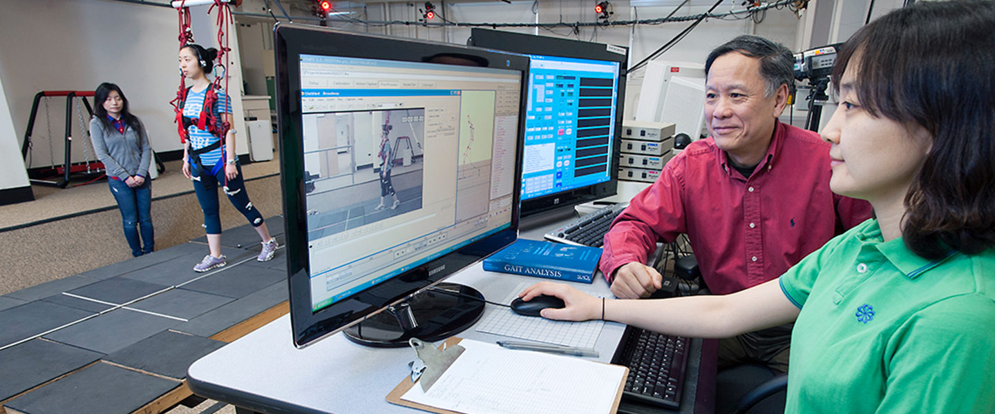 Dr. Clive Pai works at a computer with a female student in his rehabilitation lab while a patient is hooked up to harness, being supervised by another lab assistant