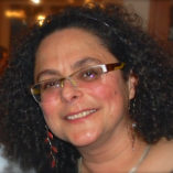 Head of smiling woman with curly hair and glasses.