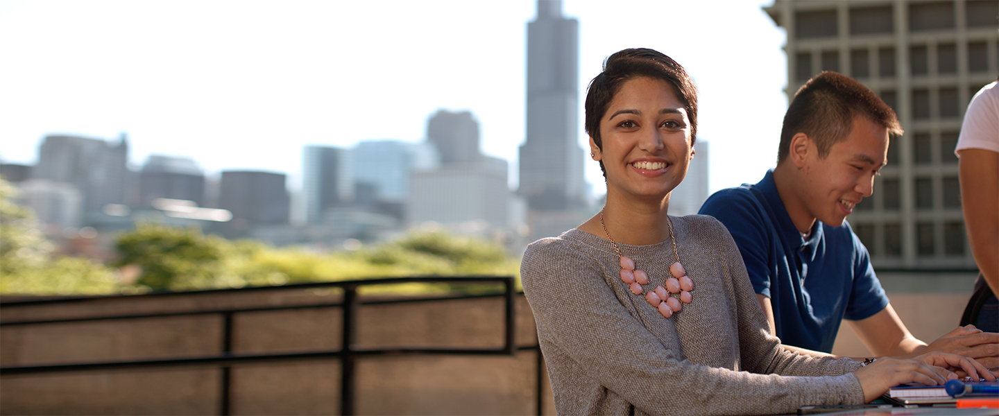 a woman sits outside and smiles at the camera with the city skyline in the background