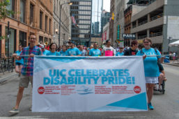 "Parade marchers hold a banner that reads, ""UIC Celebrates Disability Pride"""