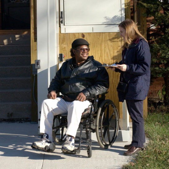 ATU staff member assisting man in wheelchair with home assessment and evaluation