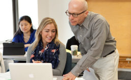 A professor instructing a student at a computer