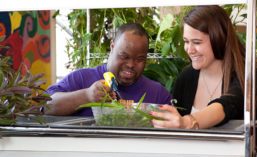 An occupational therapist in a greenhouse with African American man with disabilities