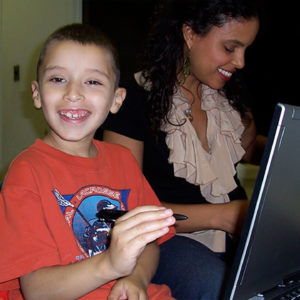 Family Clinics staff member teaching child how to work with tablet computer