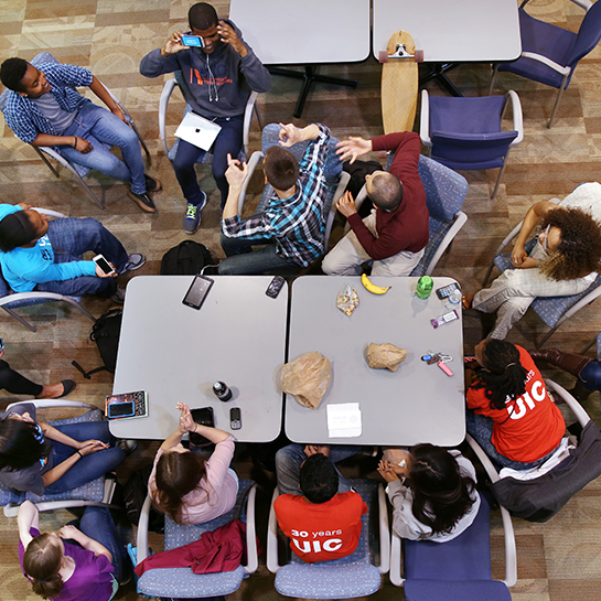 A diverse group of students hanging out around a table, viewed from above