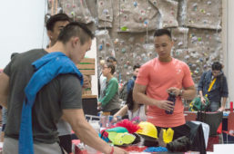 Group of students stand in front of climbing wall in gym