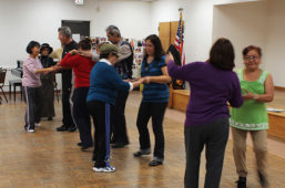 David Marquez and dance instructor teaching class of older Latinos how to dance