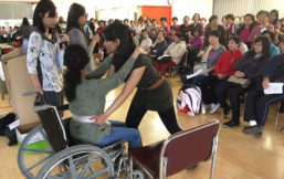 Student demonostrating how to properly lift patient from wheel chair