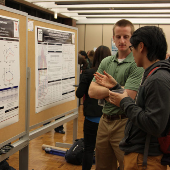 Two men talk as they stand before a researh poster