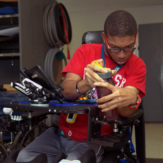 An ATU wheelchair-bound client tests a new assistive device installed on hiw sheelchair to hold items such as water bottles