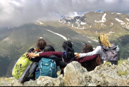 Five students place their arms around one another while looking toward a mountain valley